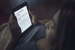 Ablesen eines ebook im Bett lizenzfreies stockbild