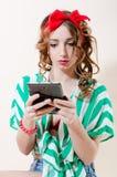 Ablesen u. des Tabletten-PC-Computers schönes blondes mit den roten Lippen u. Band auf ihrem Kopf auf hellem Hintergrund halten P Lizenzfreie Stockfotos