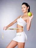 Abnehmen der Frau mit einem messenden Band und einem Apfel Stockfotografie