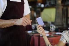 Abnehmer, der mit Kreditkarte an der Gaststätte zahlt Stockbild