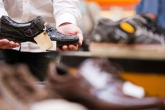 Abnehmer, der modernen Schuh am Supermarkt anhält Stockbilder