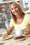 Abnehmer, der Scheibe des Kuchens und des Kaffees im Kaffee genießt Lizenzfreie Stockfotos