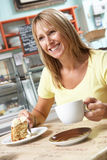 Abnehmer, der Scheibe des Kuchens und des Kaffees im Kaffee genießt Lizenzfreies Stockbild