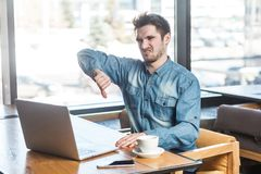 Abneigung! Seitenansichtporträt des bärtigen jungen Freiberuflers der negativen Kritik im Blue Jeans-Hemd sitzen im Café und stel lizenzfreie stockfotos