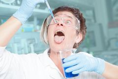 Abnormal behavior. A Chemist is showing an abnormal behavior in her laboratory Royalty Free Stock Photography