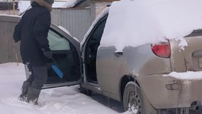 Abnormal snowfalls, climate change, a man cleans the car from snow. stock footage