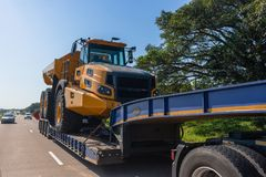 Abnormal Trucking Carrier Highway. Abnormal vehicle carrier haulage low bed trailer delivery transportation of new large heavy industrial mining construction Royalty Free Stock Images