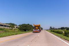 Abnormal Trucking Carrier Highway. Abnormal vehicle carrier haulage low bed trailer delivery transportation of new large heavy industrial mining construction Stock Photo