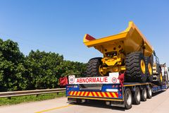Abnormal Trucking Carrier Highway. Abnormal vehicle carrier haulage low bed trailer delivery transportation of new large heavy industrial mining construction Stock Images