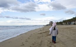 Abnutzungsjacke und -schal des kleinen Mädchens gehen auf Sandstrand nahe medite Lizenzfreie Stockbilder