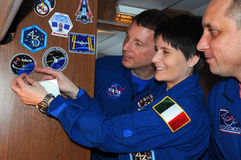 Aboard Aircraft. ISS Expedition 42/43 crewmembers T.Virts (left), S.Cristoforetti (center) and A.Shkaplerov (right) affix a decal aboard aircraft on the way to Stock Photo