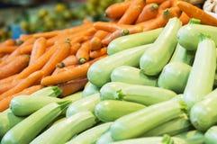 Abobrinha e cenouras verdes colhidos frescos no mercado Foco seletivo do fundo vegetal imagem de stock royalty free