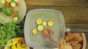 Abobrinha verde novo fritado na manteiga em uma bandeja da grade vídeos de arquivo