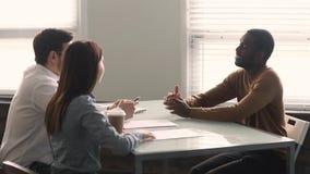 Abogado afroamericano que consulta a clientes caucásicos de los pares en el encuentro metrajes