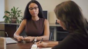 Abogado afroamericano que presenta el contrato para madurar al cliente femenino almacen de video