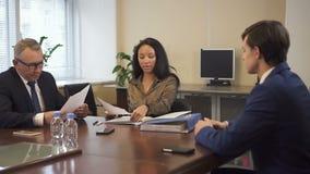 Abogado afroamericano que presenta el documento jurídico al hombre de negocios mayor y al ejecutivo joven metrajes