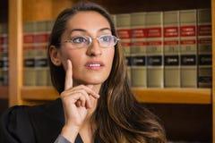 Abogado bonito que piensa en la biblioteca jurídica Imágenes de archivo libres de regalías