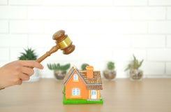 abogado con el mazo del juez que golpea el modelo de la casa disput de las propiedades inmobiliarias imagen de archivo