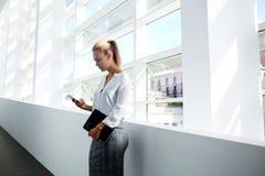 Abogado de sexo femenino profesional joven que usa el teléfono móvil y sosteniendo la almohadilla táctil foto de archivo