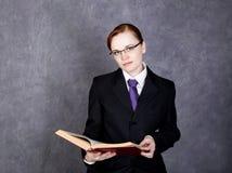 Abogado de sexo femenino que sostiene un libro grande con la expresión seria, la mujer en un traje del ` s del hombre, el lazo y  foto de archivo libre de regalías