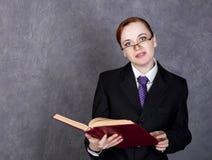 Abogado de sexo femenino que sostiene un libro grande con la expresión seria, la mujer en un traje del ` s del hombre, el lazo y  imagenes de archivo