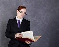 Abogado de sexo femenino que sostiene un libro grande con la expresión seria, la mujer en un traje del ` s del hombre, el lazo y  imagen de archivo