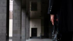 Abogado joven del hombre de negocios en caso clásico del control del traje con los documentos y cierre de la cámara lenta del pas metrajes
