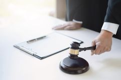 Abogado maduro que trabaja en la sala de tribunal con el martillo de la justicia a mano imagen de archivo libre de regalías