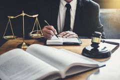 Abogado o juez masculino que trabaja con los papeles del contrato, los libros de ley y el mazo de madera en la tabla en la sala d imágenes de archivo libres de regalías