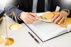 Abogado que es ofrecido recibiendo el dinero como soborno de cliente en el escritorio en sala de tribunal foto de archivo libre de regalías