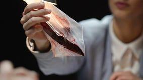 Abogado que se sostiene en pruebas sangrientas del cuchillo de las manos en la entrevista con el hombre arrestado almacen de metraje de vídeo