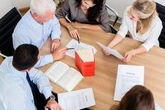 Abogados en documentos y acuerdos de la lectura del bufete de abogados Imágenes de archivo libres de regalías