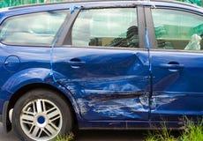 Abolladura azul del coche en una puerta imagen de archivo libre de regalías