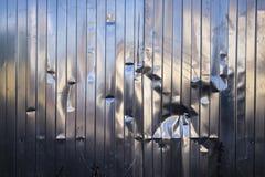 abolladura X-formada en una cerca del metal fotografía de archivo