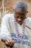 Abomey, Bénin - 7 mars 2014 : Prêtre africain de vaudou regardant en bas de concentrer tout en effectuant le rituel religieux photo libre de droits