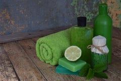 Abone la composición de la menta con cal de los productos del threatment de la belleza en colores verdes en fondo de madera marró Imagenes de archivo
