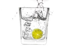 Abone la rebanada con cal que cae en un vidrio de agua Fotografía de archivo libre de regalías