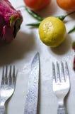 Abone las legumbres de fruta del dragón de la col de los tomates y el cuchillo de la bifurcación con cal Fotografía de archivo
