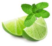 Abone las rebanadas con cal con las hojas de menta aisladas en el fondo blanco Imagen de archivo