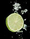 Abone (limón) caer con cal en agua Fotografía de archivo libre de regalías