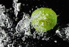 Abone (limón) caer con cal en agua en negro Imágenes de archivo libres de regalías