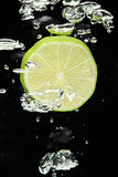Abone (limón) caer con cal en agua en negro Foto de archivo libre de regalías