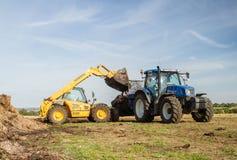 Abono de extensión del nuevo de Holanda tractor moderno del tractor en campos Foto de archivo libre de regalías