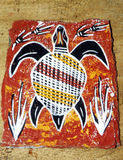 Aboriginal arts from Australia. A sample of Australian aboriginals art; a stylized swimming turtle with patterned back, surrounded by water weeds and reeds, in