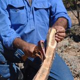 Aboriginal building a boomerang. Flinders Rangers National Park, Australia - February 09, 2002: Building a boomerang in the outback Stock Images