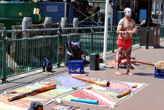 Aboriginal male street busker is giving performance with musical instruments laid out nearby on the ground at Circular Stock Photography