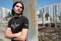 Aboriginal of the stone jungle. Young man in black t-shirt with silver skull on chain on background concrete construction Stock Photography