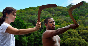 Aboriginal warrior man teach woman tourist how to throw a boomer stock images