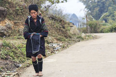 Aboriginal woman of the mountains of Sapa, in north Vietnam, dressed with the traditional attire walking to her village Royalty Free Stock Photos