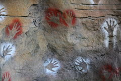 Aborigine art hands on stone wall. Replica of Aboriginal art: Many hands painted on a stone wall, that shows the traditional way of handing down land from Stock Images